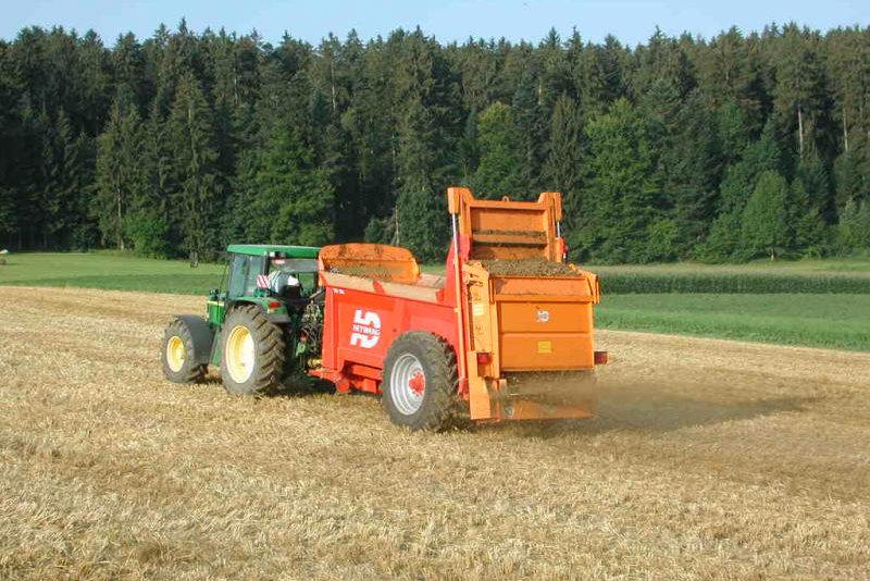 Traktor verteilt Düngekalk auf dem Feld